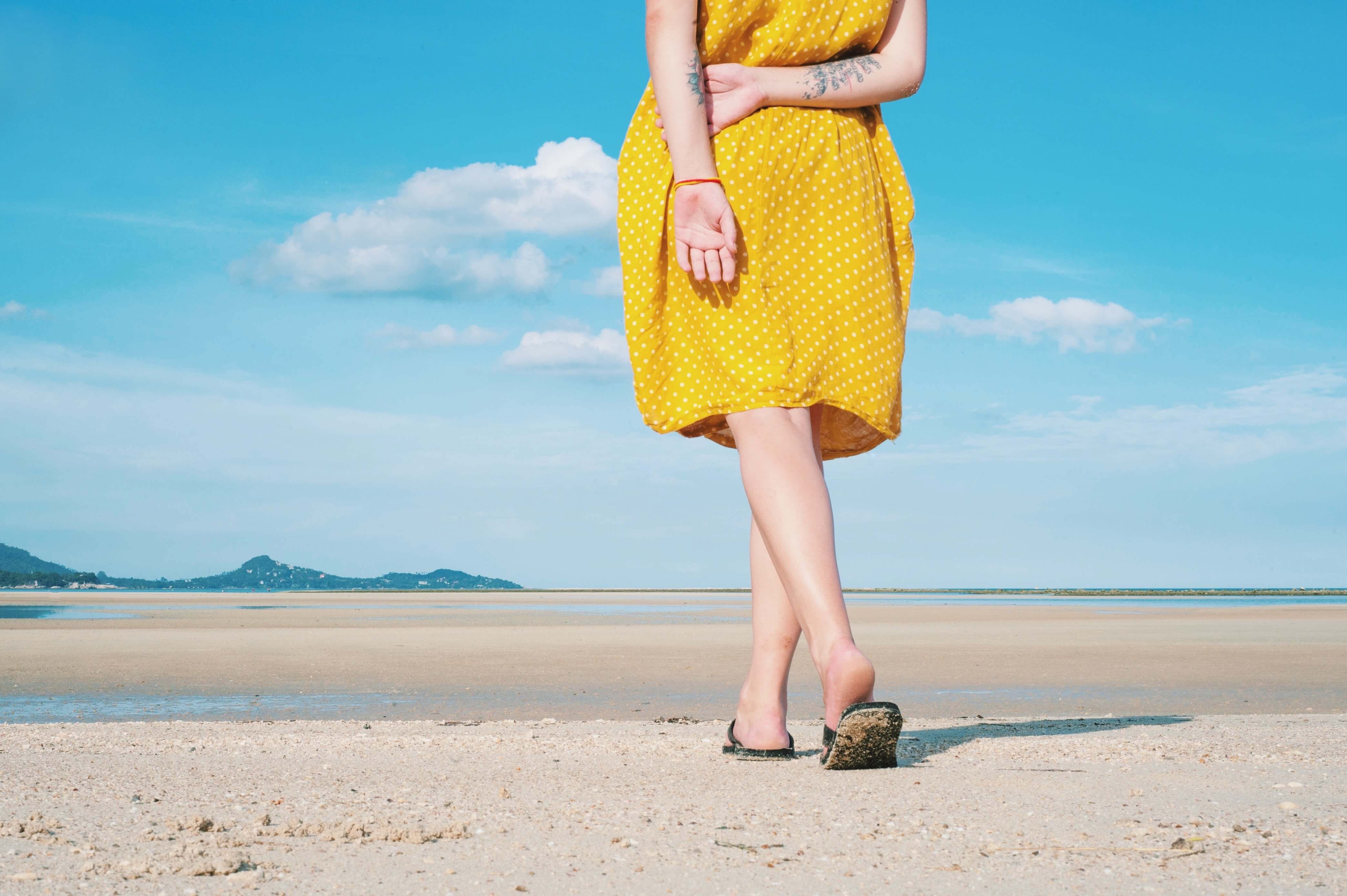 woman with yellow dress on beach, laser hair removal