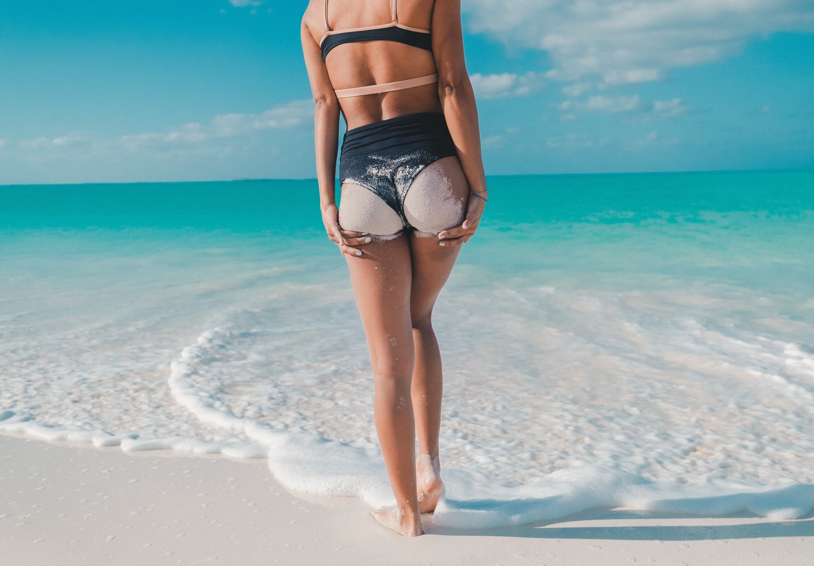 A bikini-wearing woman cheekily poses walking into the ocean.