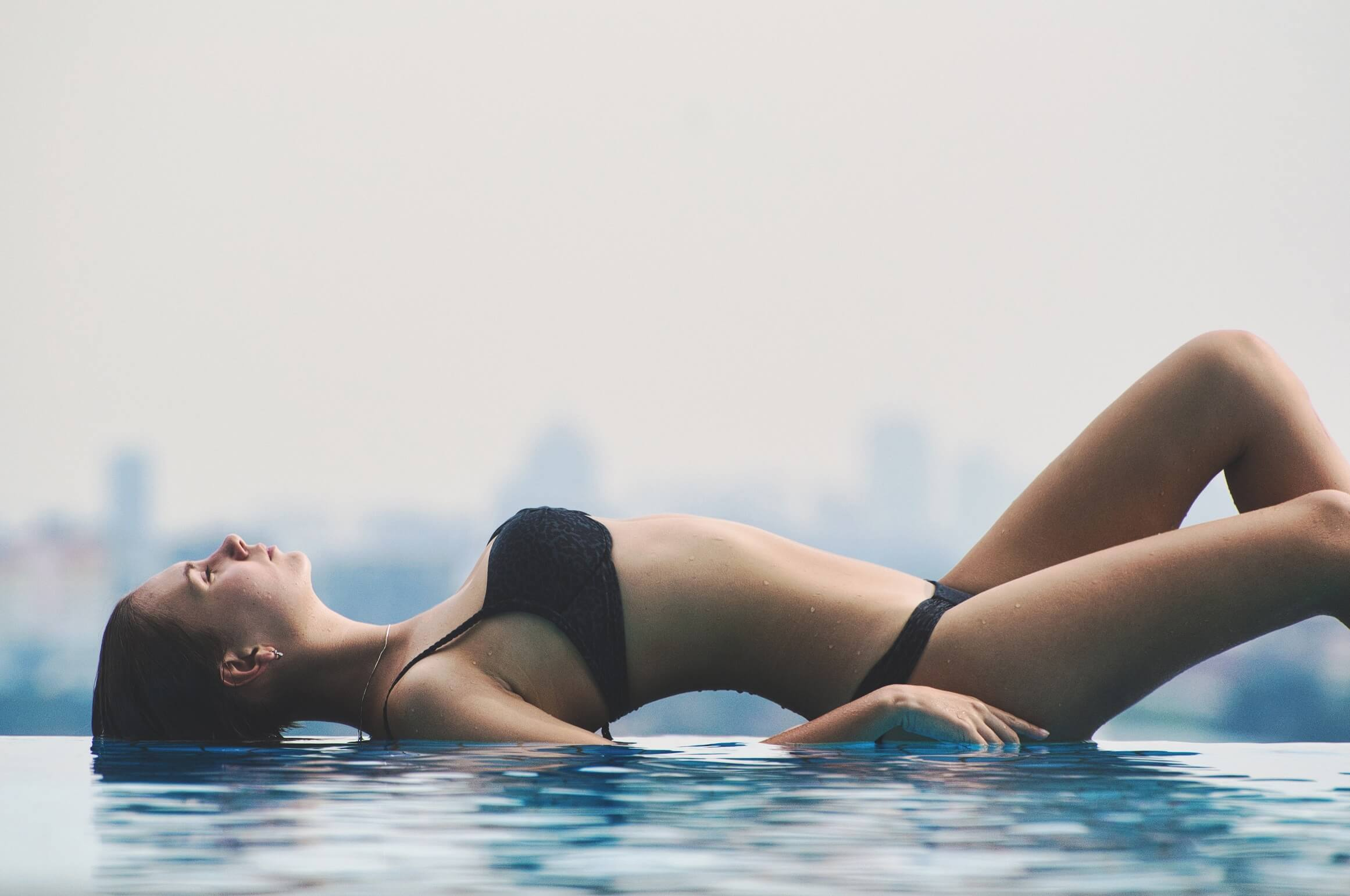 A woman wearing a bikini lies on the edge of an infinity pool provocatively. .