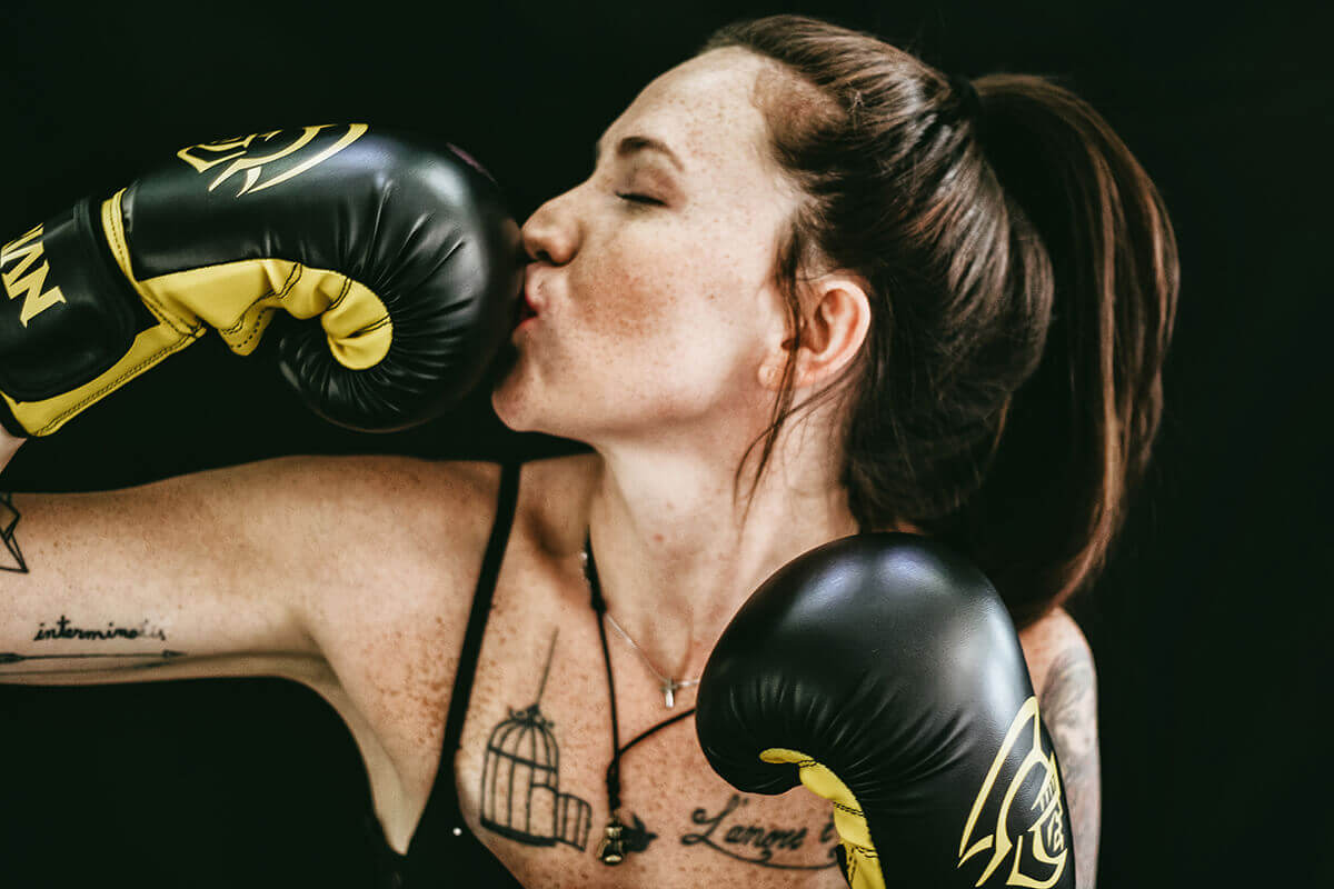 A tattooed woman in boxing gloves kisses one of the gloves with a fun smile on her face.