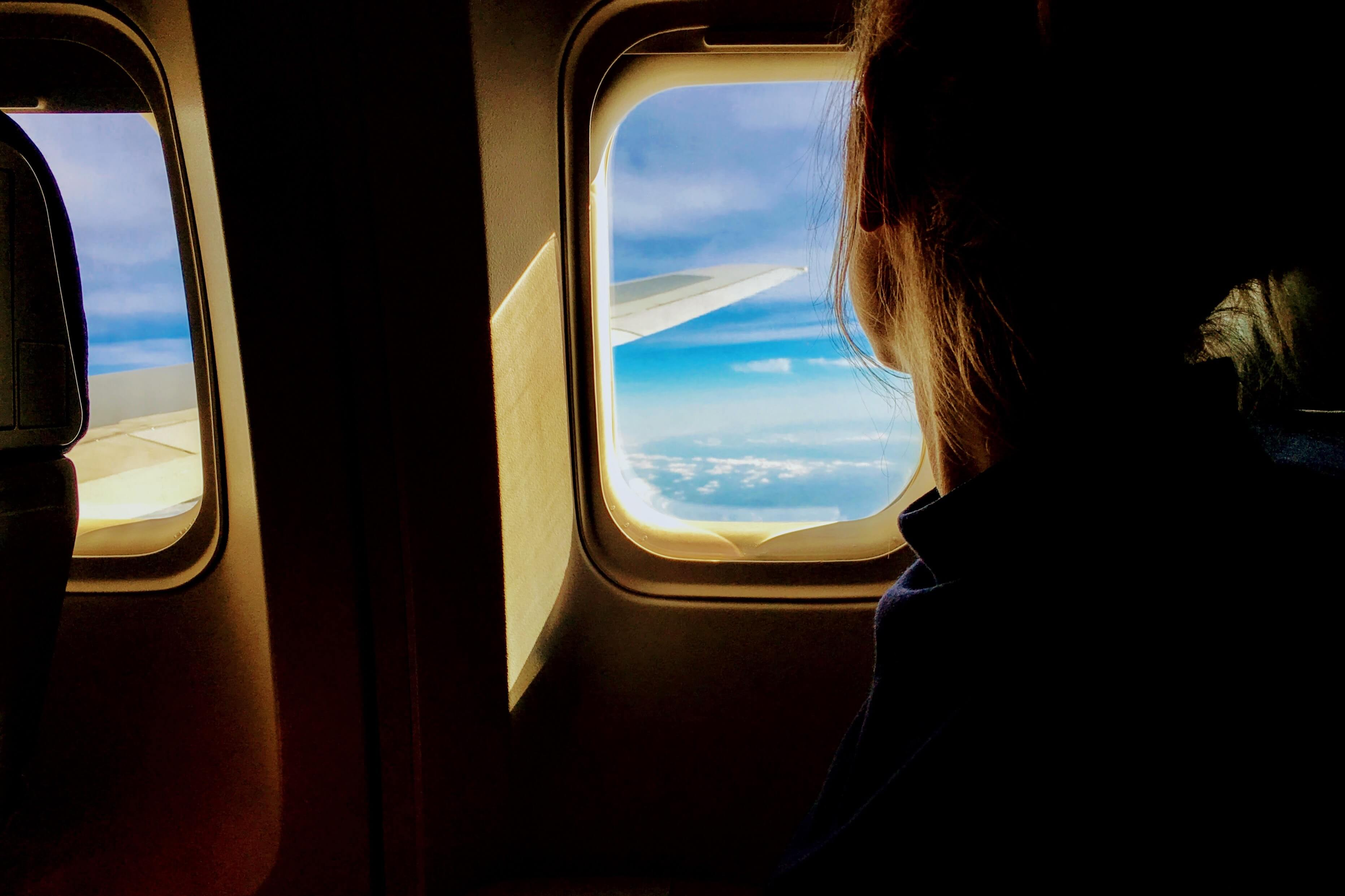 A woman looks out the window of a plan as it soars through the sky.