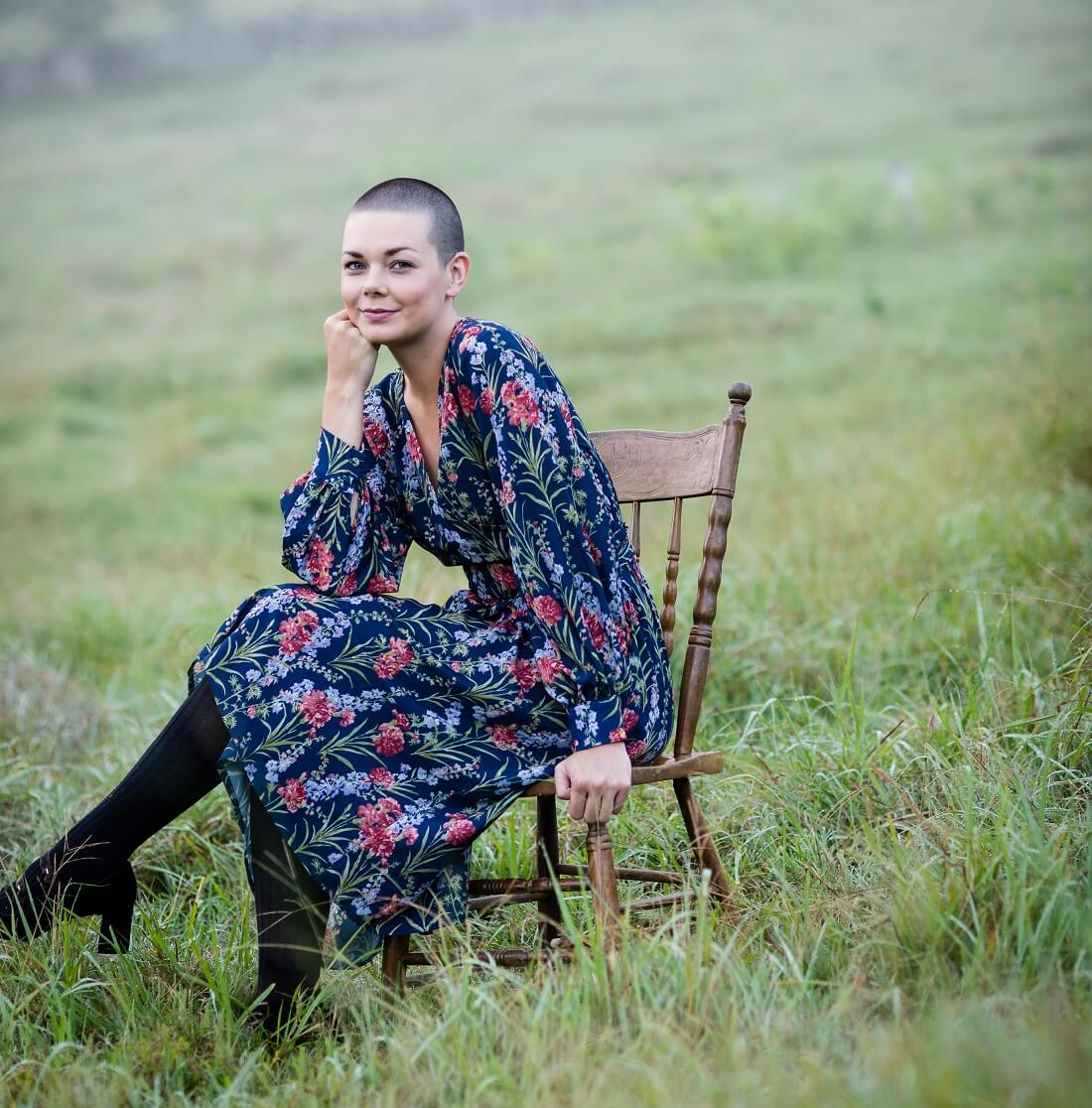 Woman who has had Micropigmentation done sits in a chair in the grass