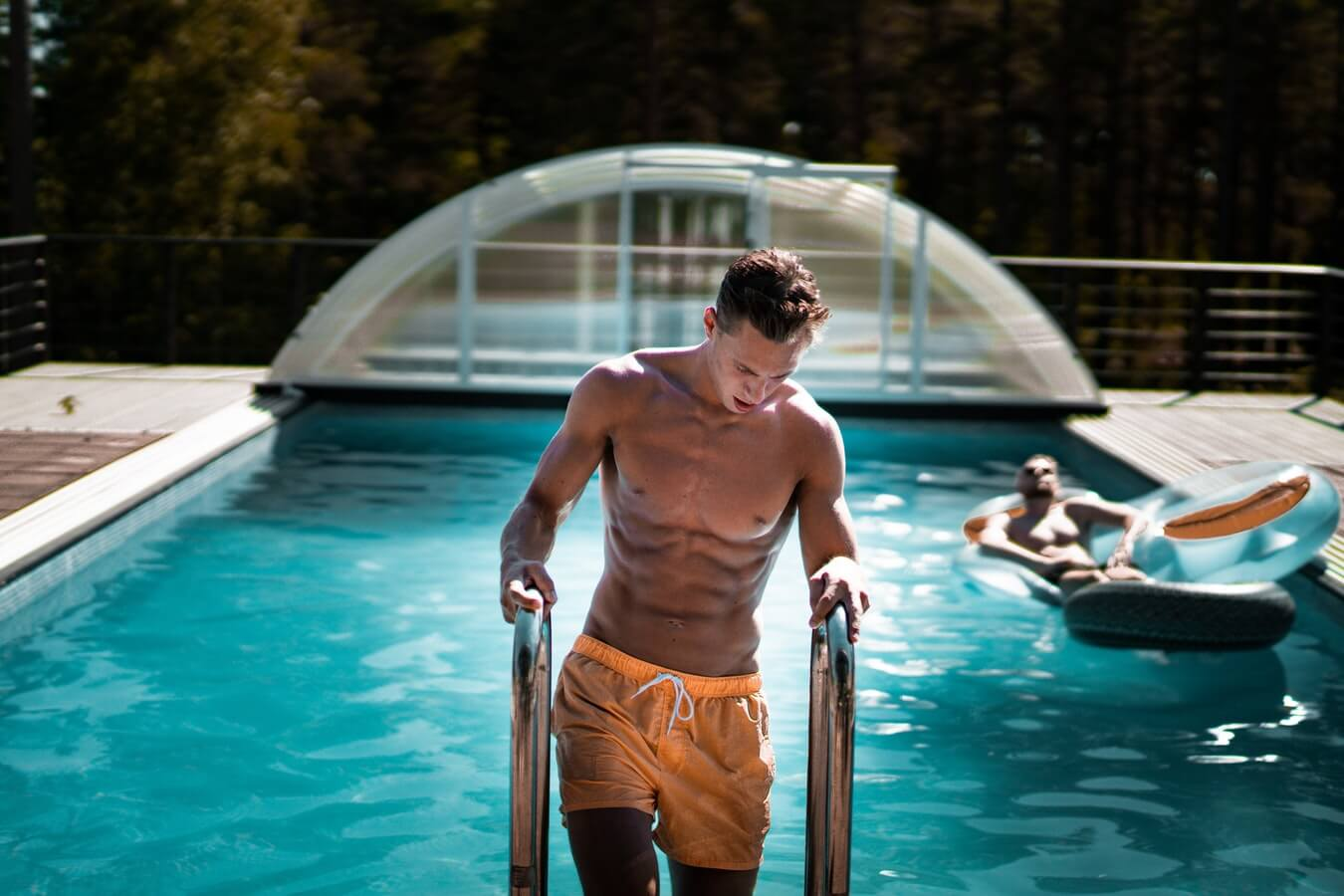 A shirtless man climbs out of a pool.